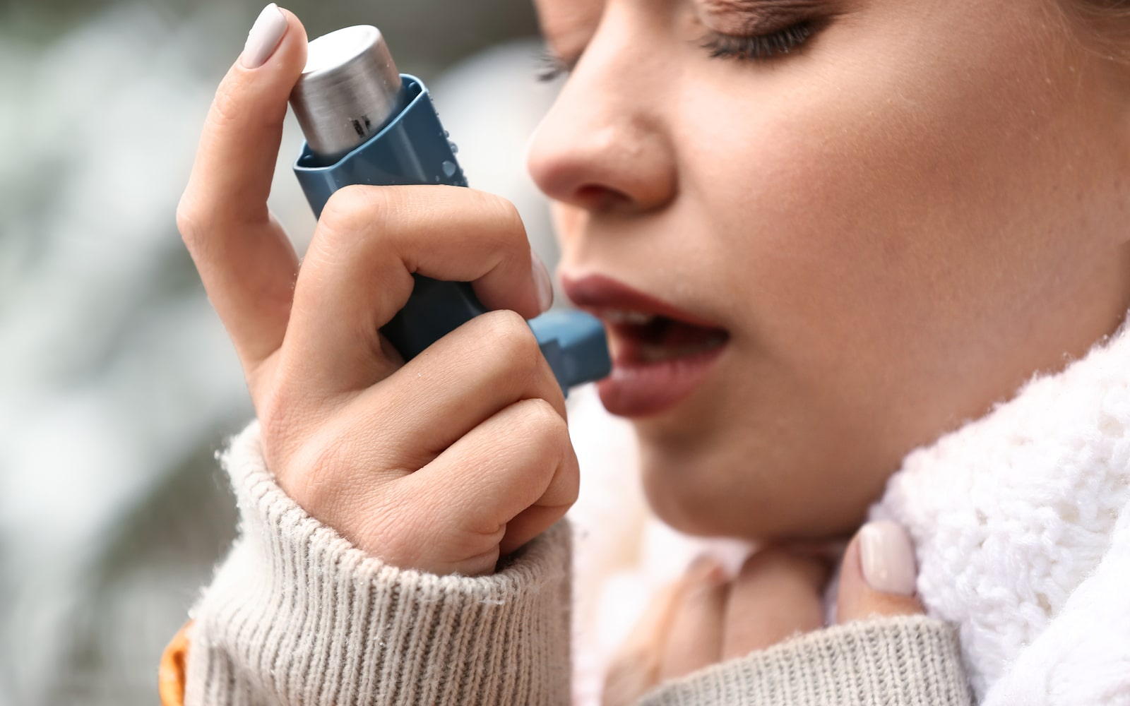 Woman using an asthma inhaler