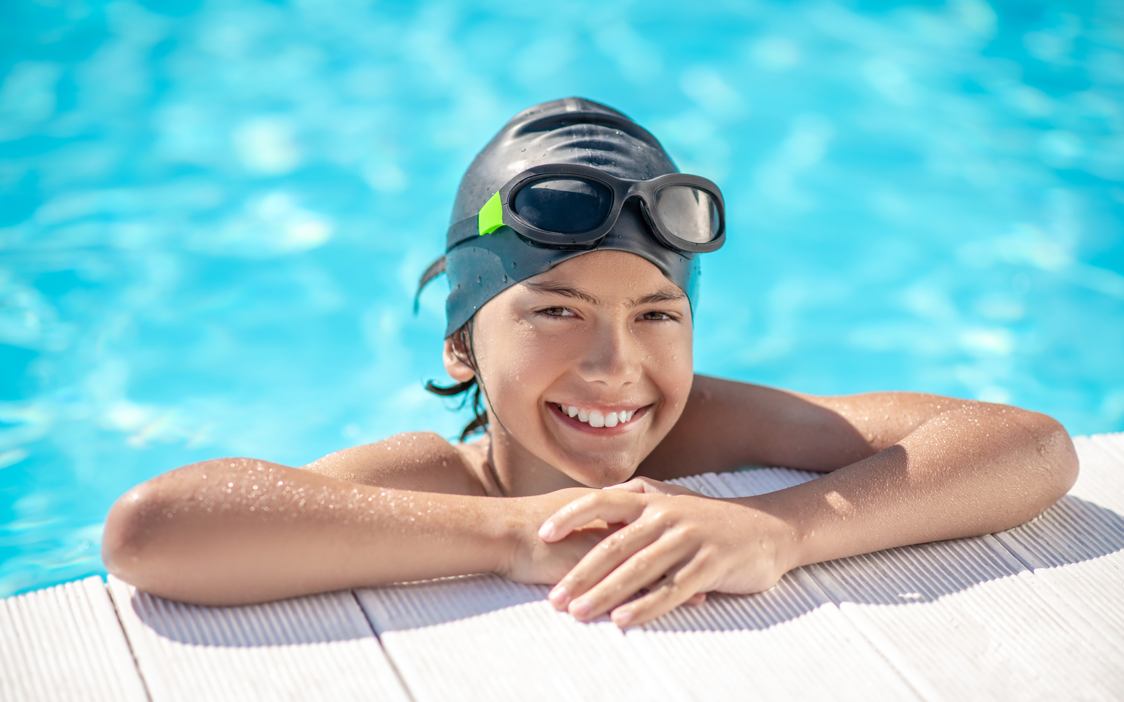 Child smiling at edge of a swimming pool